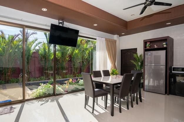 O design interno e externo da sala de estar e área para refeições em plano aberto apresenta mesa de madeira