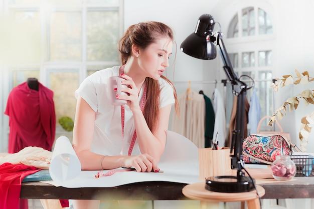 O designer de moda feminina, trabalhando no estúdio, sentado na mesa
