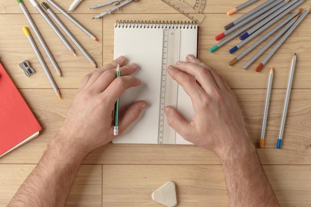 O designer desenha um esboço em um caderno sobre uma mesa de madeira. papelaria. vista de cima.