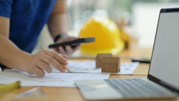O designer está calculando e editando o plano da casa para apresentar o cliente.