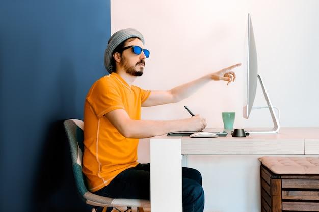 O designer gráfico aponta para a tela, usa camisa laranja, chapéu e óculos escuros