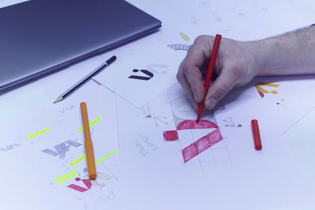 O designer gráfico projeta um logotipo sobre um fundo de esboços e desenhos em uma mesa. logotipos impressos em papel em um estúdio com um laptop.