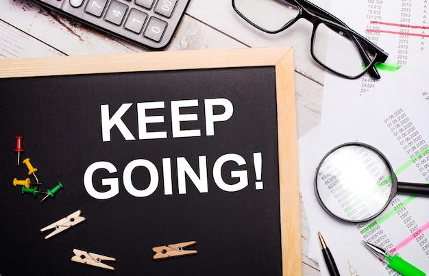 O desktop conta com calculadora, relatórios, óculos, lupa, canetas e um quadro com prendedores de roupa e texto mantenha continuando conceito de negócio.