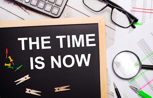 O desktop possui calculadora, relatórios, óculos, lupa, canetas e um quadro com prendedores de roupa e texto a hora é agora. conceito de negócio.