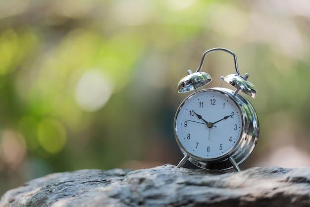 O despertador com numeral árabe no sentido horário pôs sobre a rocha no jardim verde com bokeh natural.