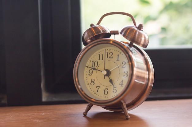 O despertador do foco seletivo é colocado no assoalho de madeira ao lado da janela.
