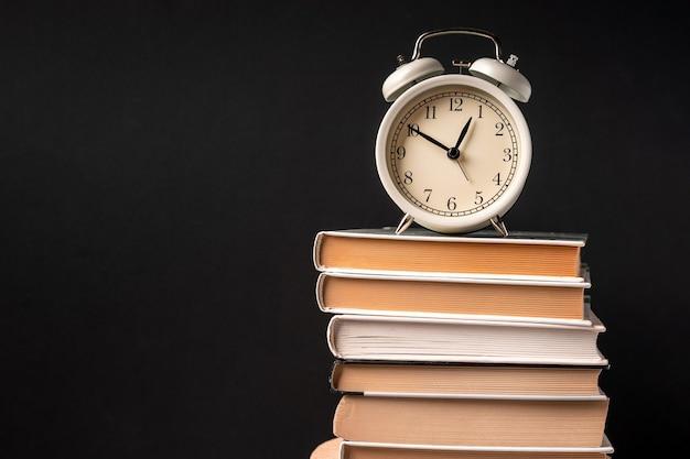 O despertador fica sobre uma pilha de livros em um fundo preto. conceito de treinamento