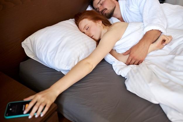 O despertador toca enquanto o casal dorme, hora de acordar de manhã