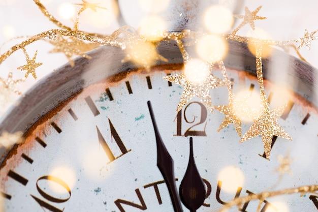 O despertador vintage está marcando meia-noite. é meio-dia, natal e bokeh, conceito festivo de feliz ano novo de feriado com luz de fundo bokeh