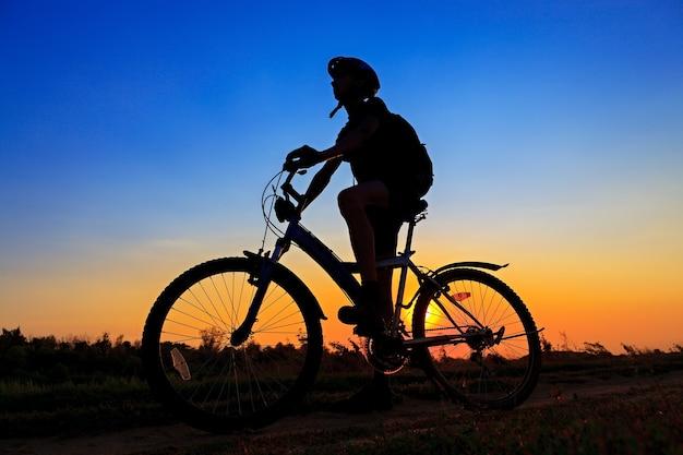 O desportista de bicicleta, viajando na estrada no fundo por do sol.