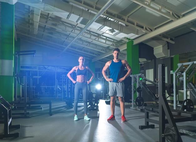 O desportista e a desportista estão no ginásio, no fundo de luz brilhante