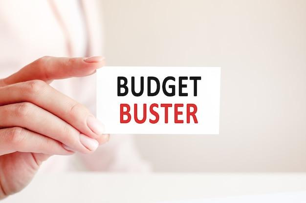O destruidor de orçamento está escrito em um cartão branco nas mãos de uma mulher. fundo rosa.