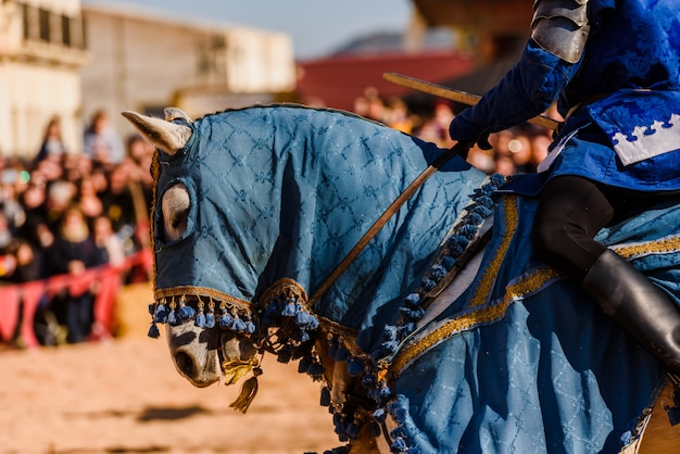 O detalhe da armadura de um cavaleiro montou a cavalo durante uma exposição em um festival medieval.