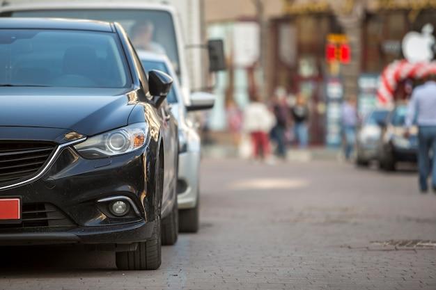 O detalhe da vista dianteira do close-up de carro estacionou no pavimento no fundo da silhueta borrada de pessoas e carros de passeio no dia de verão ensolarado.
