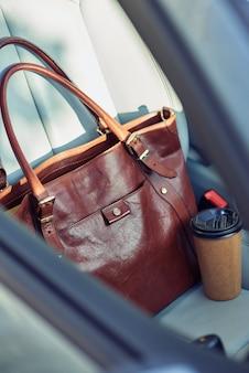 O dia começa com um café, close-up, uma foto de uma bolsa e uma xícara de café no banco do passageiro