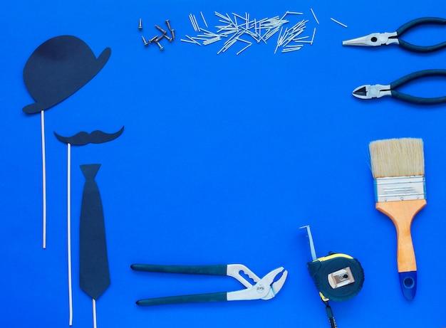 O dia de pai feliz e o laço e o chapéu coloridos das ferramentas no azul.