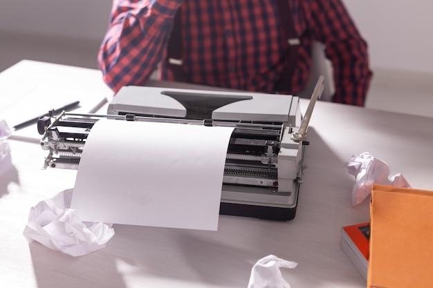 O dia do escritor e o conceito de tecnologia - escritor bonito cercado por pedaços de papel focado no trabalho
