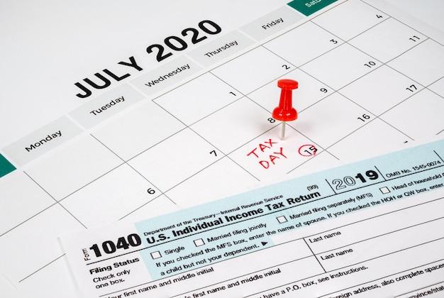 O dia do imposto foi estendido para 15 de julho por causa do covid-19. calendário de julho mostrando o formulário de retorno 1040 e o dia do imposto