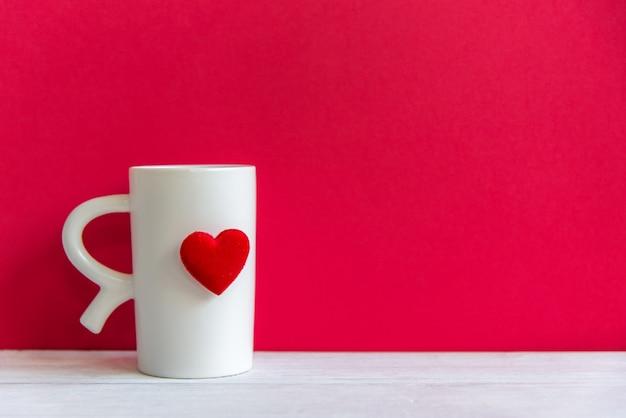 O dia dos namorados com coração branco do copo branco do café no copo, fundo vermelho da parede, copia o espaço valentine concept.