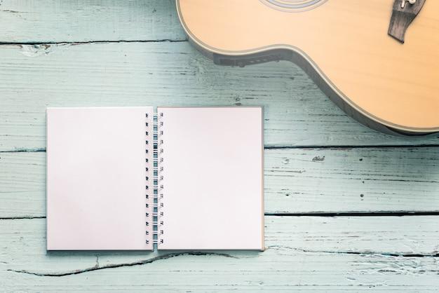 O diário apaga com um violão na mesa de madeira do compositor de música para o fundo de notas musicais