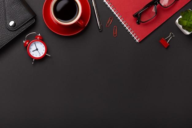 O diário vermelho da flor do despertador do bloco de notas do copo de café do fundo preto pontilha o teclado na tabela. vista superior com espaço para texto