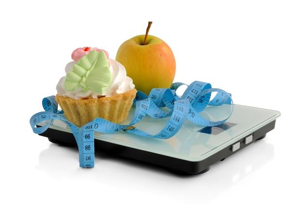 O dilema de um bolo ou uma maçã embrulhada na escala centimétrica no fundo branco isolado