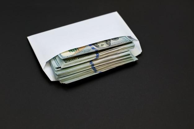 O dinheiro do dólar no envelope no bônus preto do fundo, recompensa, beneficia o conceito.