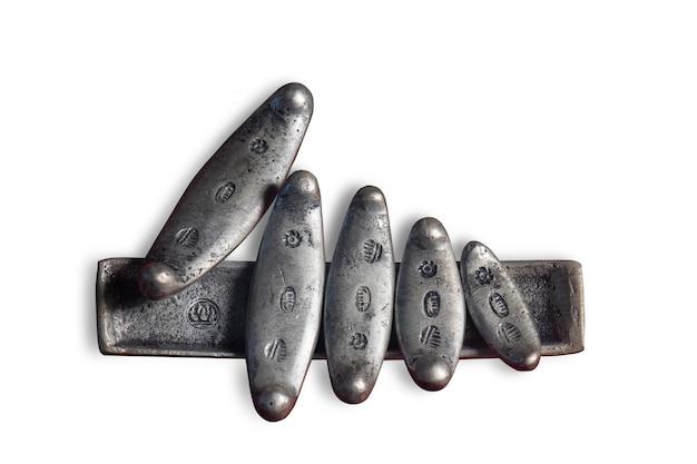 O dinheiro siamês antigo é uma barra longa e esbelta feita de prata genuína ou cobre e depois revestida com prata sobre fundo branco