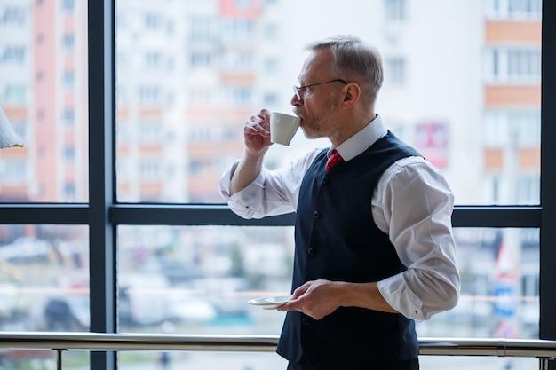 O diretor-gerente sorridente e feliz pensa no desenvolvimento de sua carreira de sucesso enquanto está em pé com uma xícara de café na mão em seu escritório, perto do fundo de uma janela com espaço de cópia