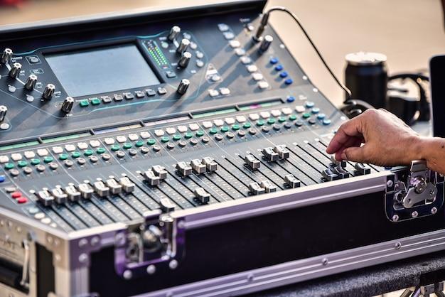 O dj está ajustando o volume do som. console de mixagem de áudio profissional