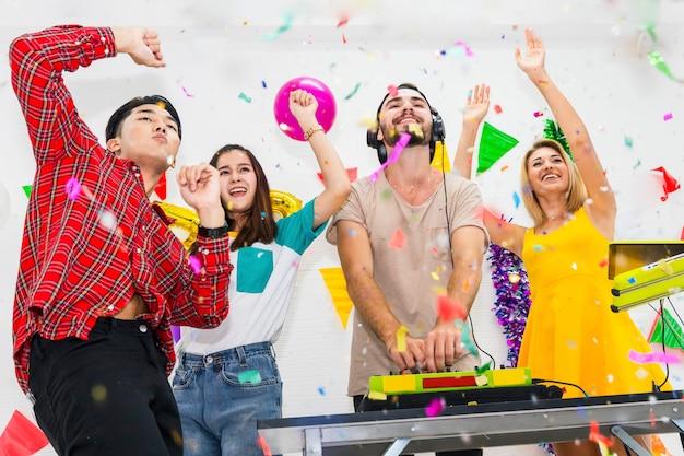 O dj joga no melhor. amizade aprecia comemorando jogando confetes ao torcer na festa na sala branca.