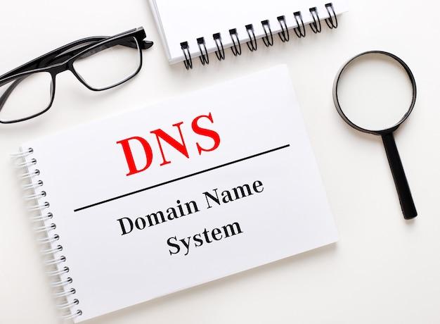 O dns domain name system é escrito em um notebook branco sobre uma superfície clara perto do notebook, óculos de armação preta e uma lupa