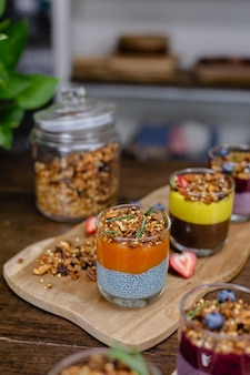 O doce colorido do café da manhã saudável deserta alguns pudins de chia diferentes em potes de vidro na mesa de madeira na cozinha em casa.