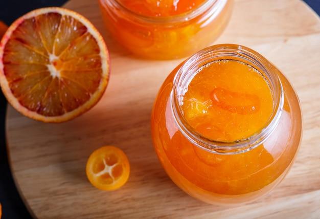 O doce da laranja e do kumquat em um frasco de vidro com frutos frescos em uma cozinha de madeira embarca.