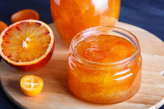 O doce da laranja e do kumquat em um frasco de vidro com frutos frescos na cozinha de madeira embarca.