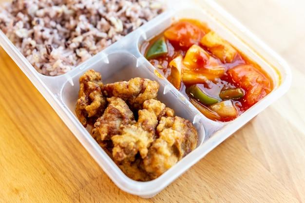 O doce e o ácido orgânicos denominados tailandeses fritaram com a baga da carne de porco e do arroz na caixa do produto comestível.