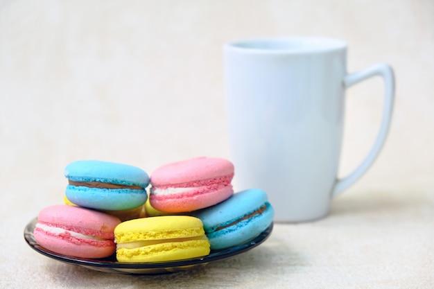 O doce francês colorido endurece bolinhos de amêndoa em uma placa de vidro e em uma caneca de café branco.
