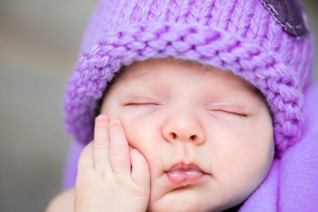 O doce sonho de um recém-nascido de chapéu roxo