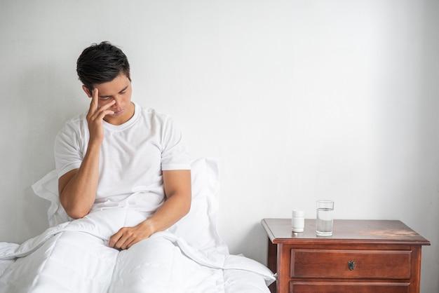 O doente estava sentado na cama, tocando sua cabeça com a mão.