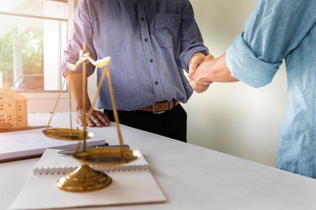 O dono da casa aperta as mãos com o advogado. plano de lei de habitação bem sucedido.