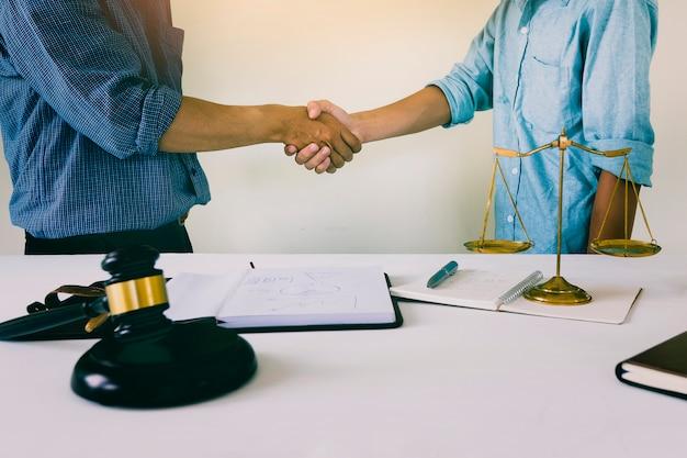 O dono da casa aperta as mãos com o advogado. plano de lei de moradias bem sucedido