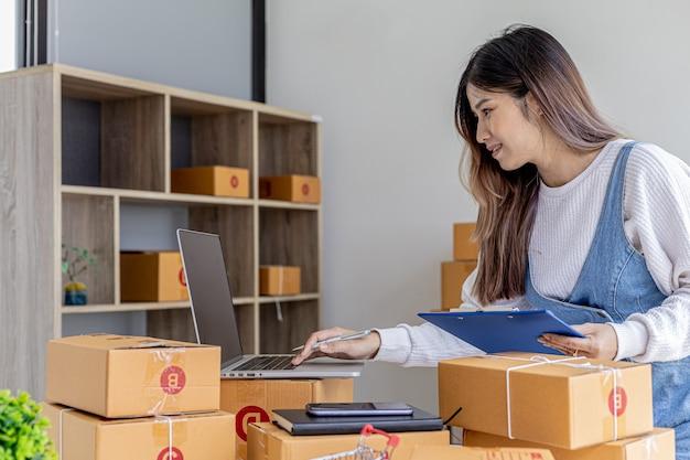 O dono da loja online está verificando o valor da compra no laptop e preparando a entrega, pacote para embalagem da mercadoria. venda online e conceitos de compras online.