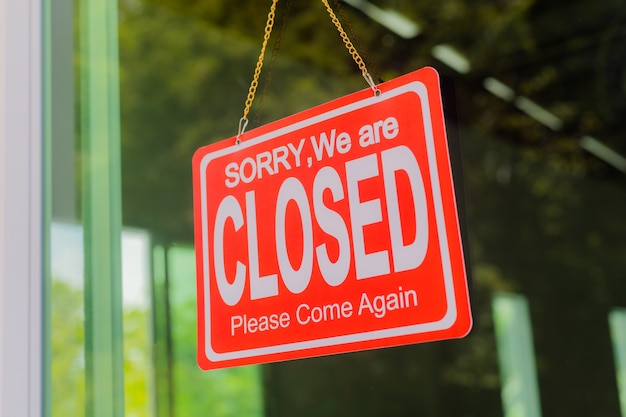 O dono da loja pendura uma placa para fechar o negócio em frente à porta.