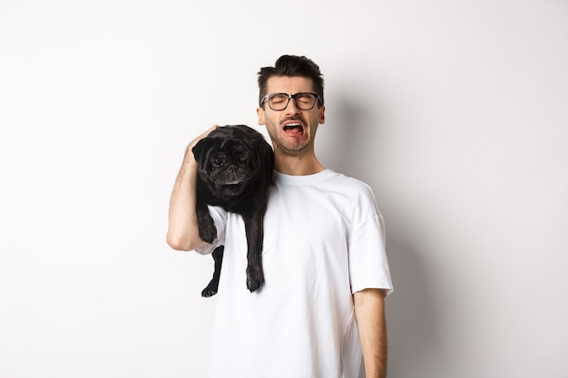 O dono do cachorro triste chorando, segurando um lindo pug preto no ombro e parecendo infeliz, soluçando enquanto fica de pé sobre o branco.