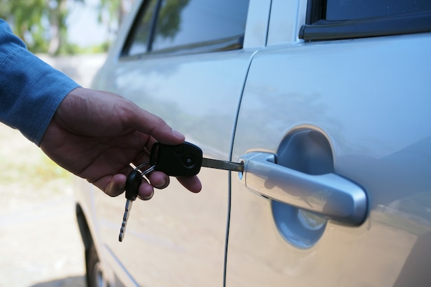 O dono do carro usa a chave para abrir a porta do carro.