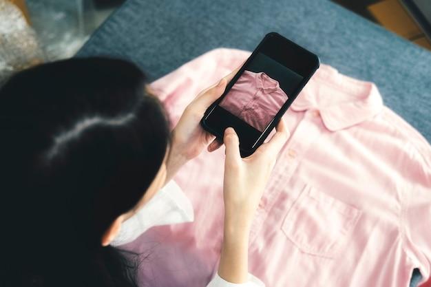 O dono do vendedor on-line tira uma foto do produto para fazer o upload para a loja on-line do website.