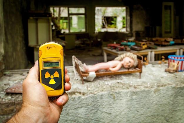 O dosímetro nas mãos com o nível de radioatividade no prédio abandonado do jardim de infância após a explosão do reator pripyat, chernobyl.