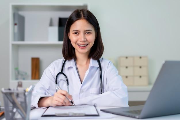 O doutor asiático de sorriso está vestindo um estetoscópio no escritório.