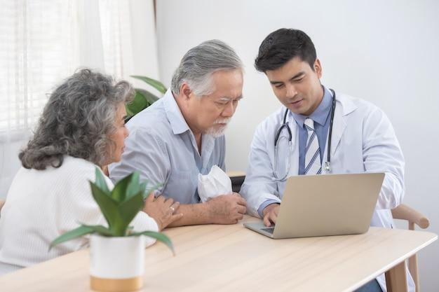 O doutor caucasiano usa o laptop e conversa com o paciente masculino asiático velho sobre o sintoma da doença, exame de saúde idoso acima em casa.