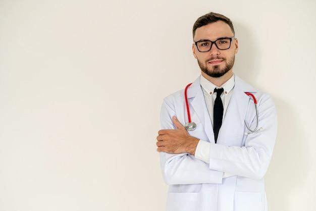 O doutor considerável novo com braços cruzou a posição no fundo branco.